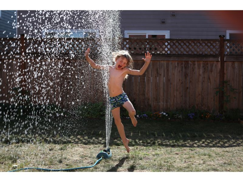 boy-jumping-through-sprinklers
